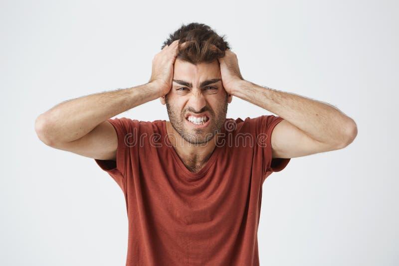 Boos knap Kaukasisch mannetje in rode t-shirt die gekke uitdrukkingen hebben, die hoofd met handen boos van mensen drukken royalty-vrije stock afbeeldingen