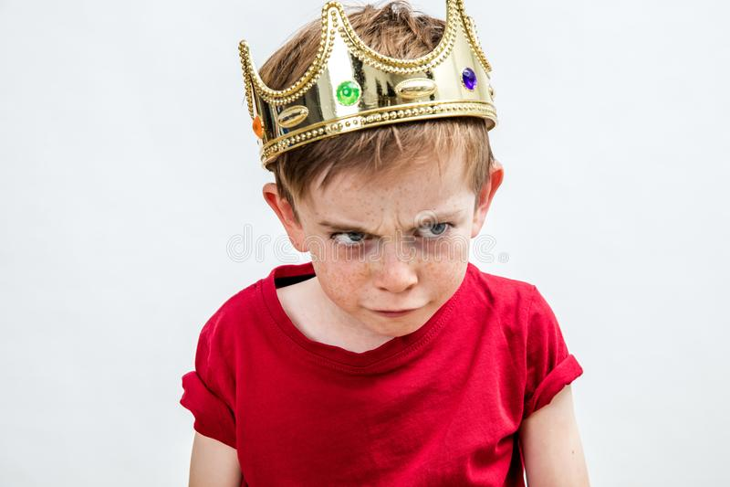 Boos mooi bedorven jong geitje die koningskroon dragen die ongelukkig ouderschap onder ogen zien royalty-vrije stock foto's