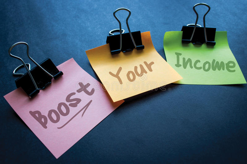 Boost your Income. Boots income concept on sticky notes and black background stock image