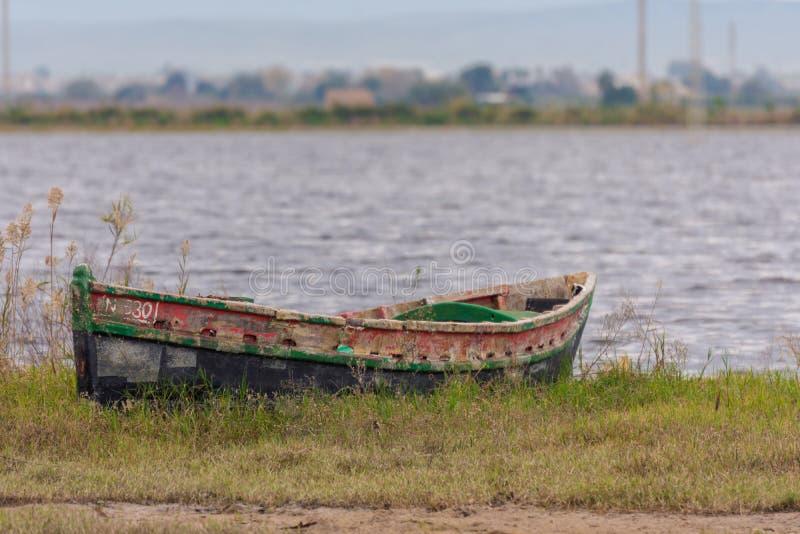 Boot angeschwemmt auf dem Ufer der Lagune im Naturpark von Albufera, Valencia, Spanien lizenzfreie stockfotografie