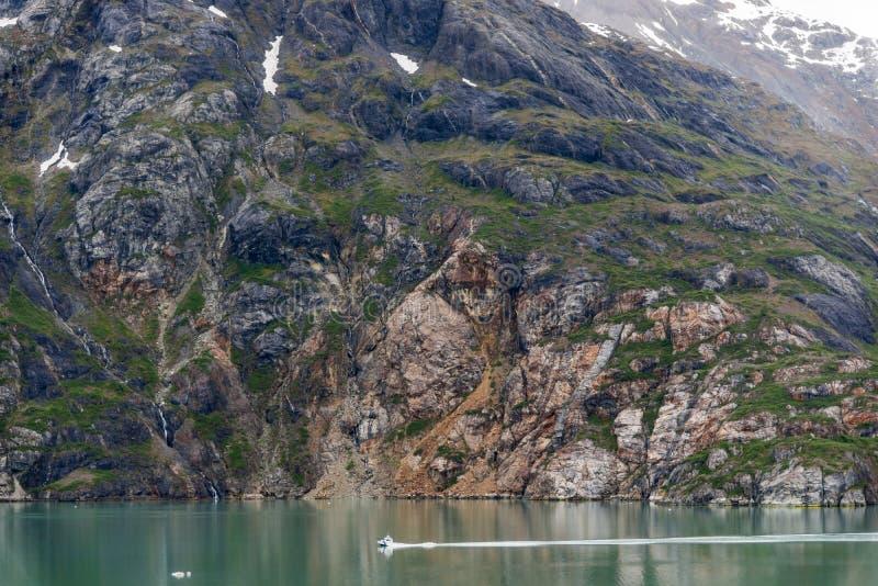 Boot auf dem Ozean mit Gebirgshintergrund und bewölktem Himmel bei Glacier Bay Alaska lizenzfreie stockfotografie