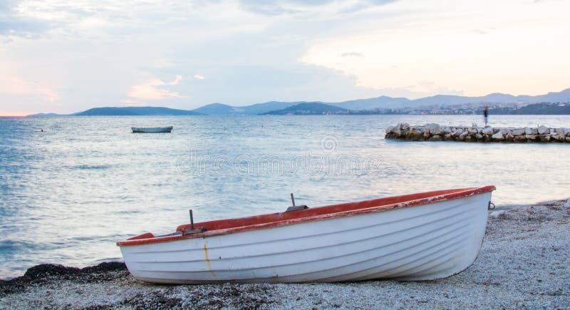 Boot auf dem Ozeanstrand an der Dämmerung, Spalte, Kroatien lizenzfreie stockfotos