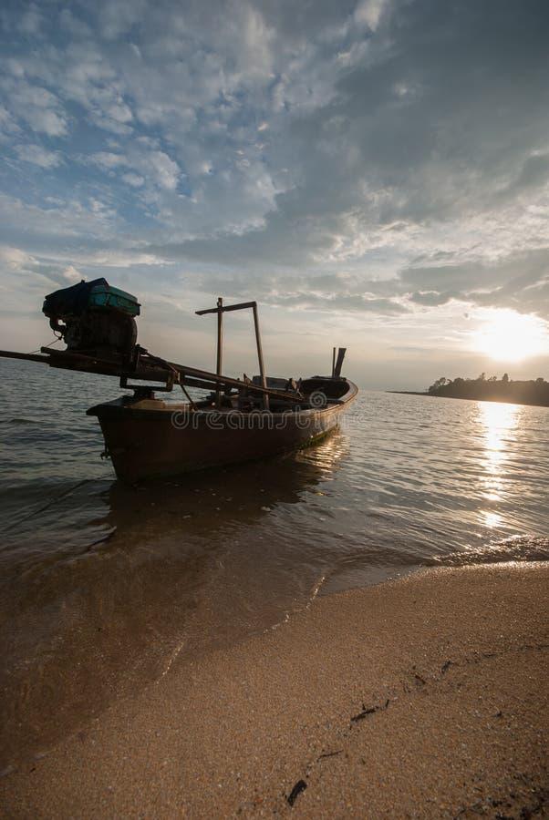 Boot auf dem Strand bei Sonnenaufgang in der Gezeitenzeit stockfoto