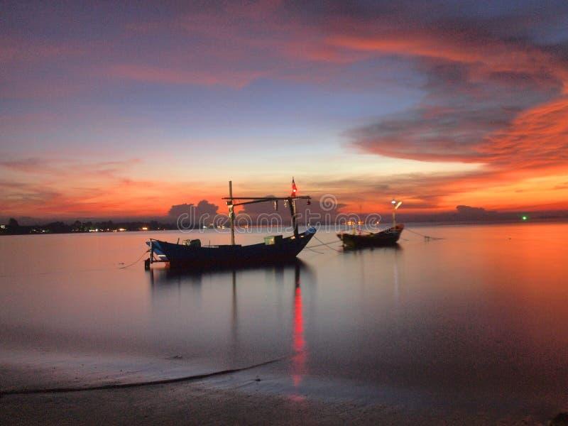 Boot auf dem Strand bei Sonnenaufgang in der Gezeitenzeit lizenzfreie stockfotos