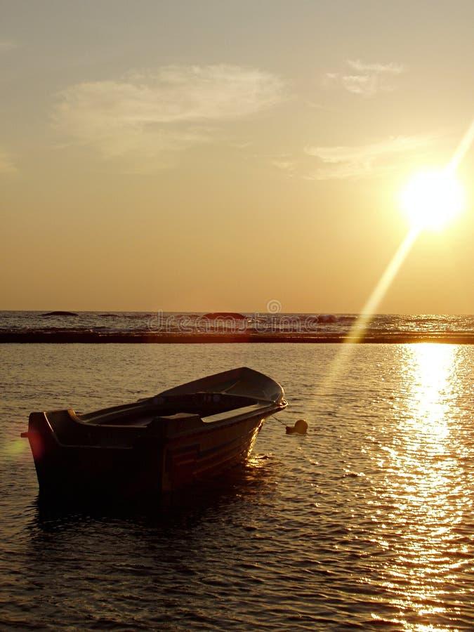 Boot auf Meer am Sonnenuntergang lizenzfreie stockbilder