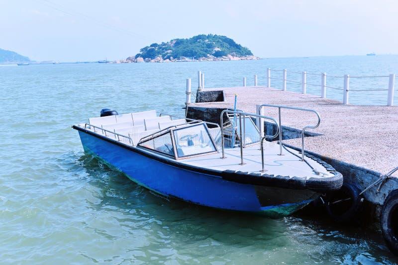 Boot bij de kustpijler die wordt gedokt stock afbeeldingen