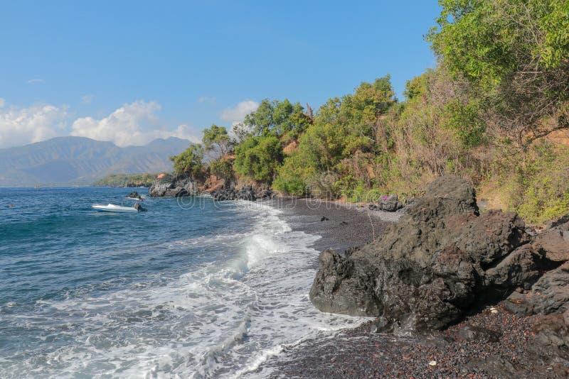 Boot bij het strand met zwarte zand en lavarotsen wordt verankerd die Dichte olievegetatie en bergketen op achtergrond met witte  royalty-vrije stock foto's