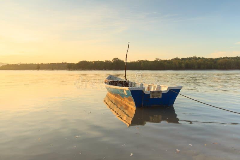 Boot bij zonsopgang met bezinning in Buntal-Dorp stock afbeeldingen