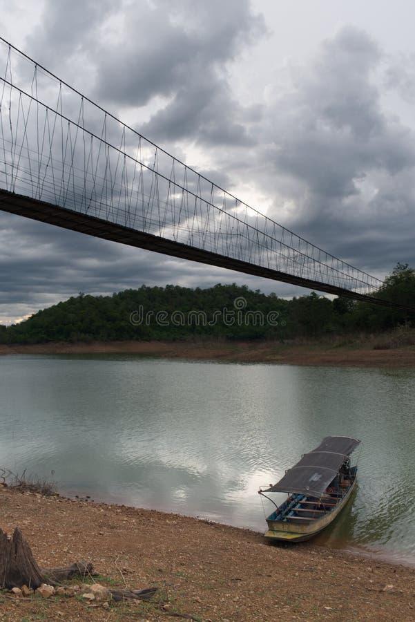 Boot, das auf Ufer von einem See unter hängender Brücke im Nationalpark, Thailand sitzt stockfoto