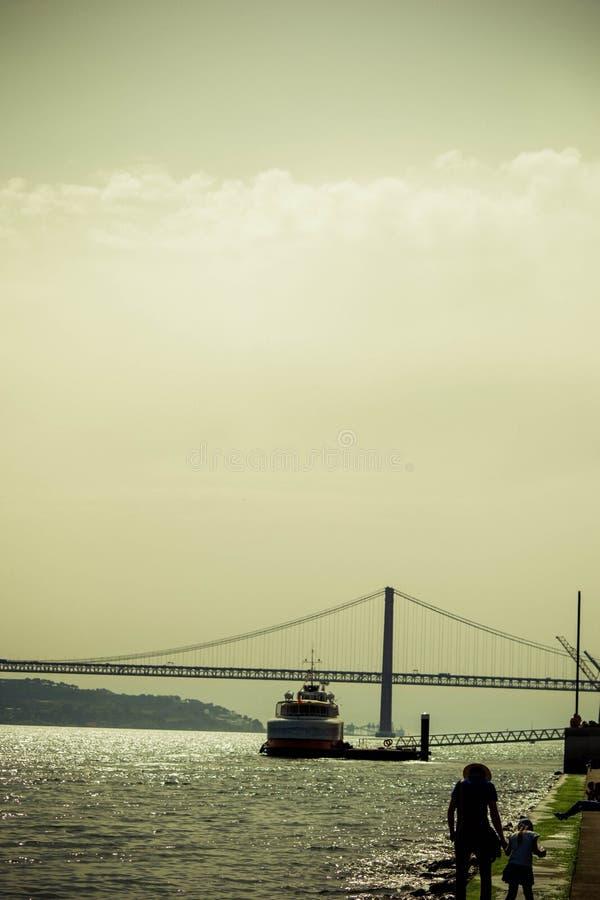 Boot, das eine Brücke in Tejo Lissabon kreuzt stockfotografie