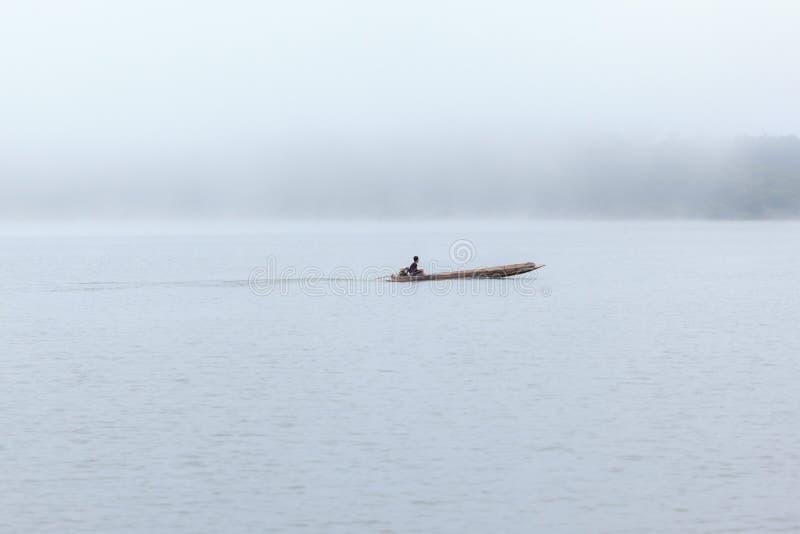 Boot des langen Schwanzes mit einem Fischer nach innen auf Fluss mit nebeligem Hintergrund stockfoto