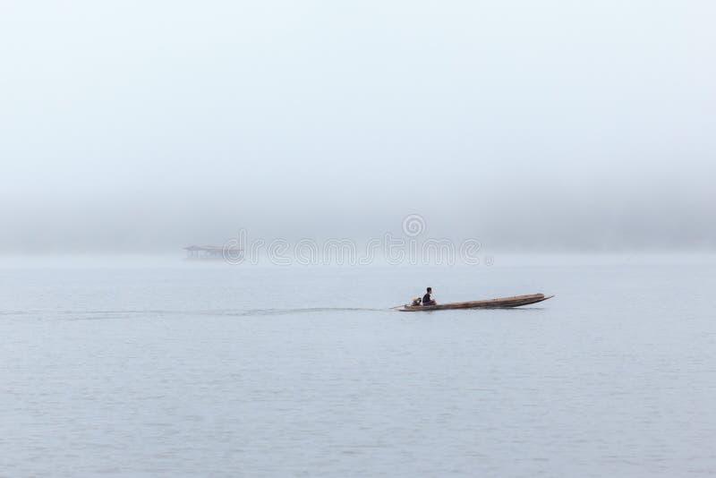 Boot des langen Schwanzes mit einem Fischer nach innen auf Fluss mit nebeligem Hintergrund lizenzfreies stockfoto