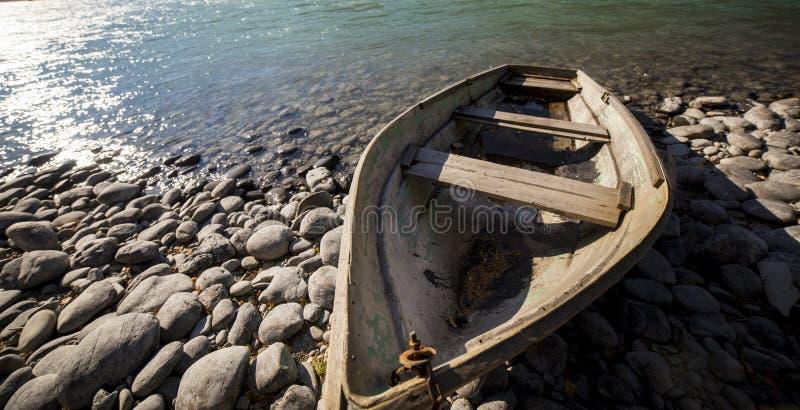 Boot dichtbij bergrivier stock afbeeldingen