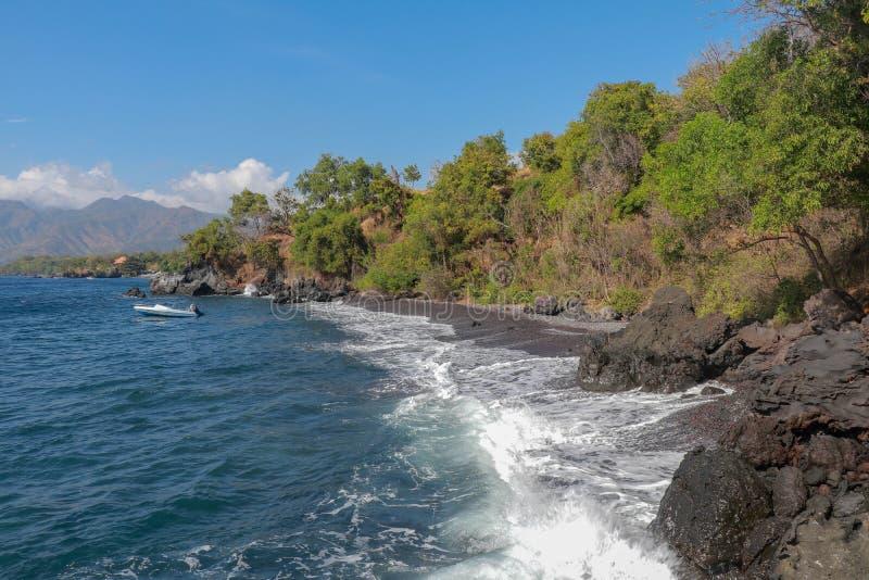 Boot die bij het strand met zwarte zand en lavarotsen wordt verankerd Dichte olievegetatie en bergketen op achtergrond met witte  stock foto's