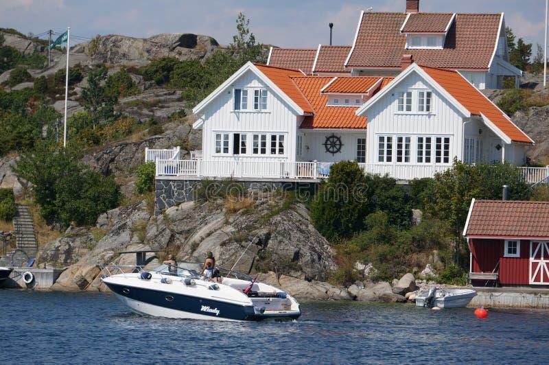 Boot die voor het huis, Noorwegen wordt vastgelegd stock fotografie