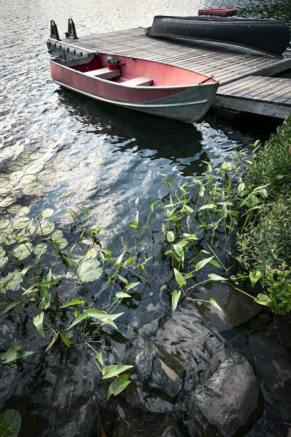 Boot am Dock auf kleinem See lizenzfreies stockbild