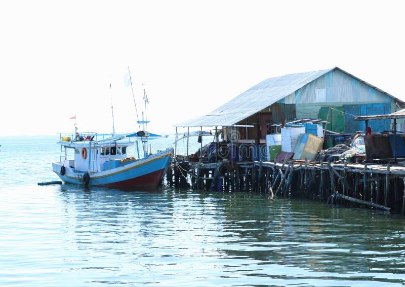 Boot door een huis in Sorong stock foto's