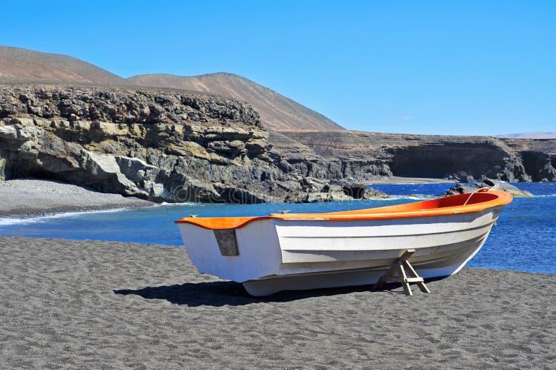 Boot in een zwart zandstrand in Fuerteventura, Spanje royalty-vrije stock afbeelding