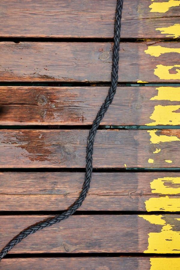 Boot en jachtkabel op natte houten havenplanken royalty-vrije stock fotografie