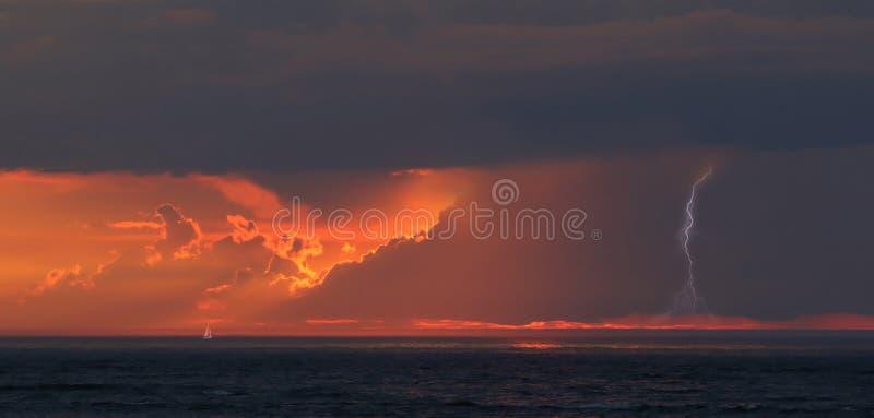Boot en onweer bij zonsondergang royalty-vrije stock afbeelding