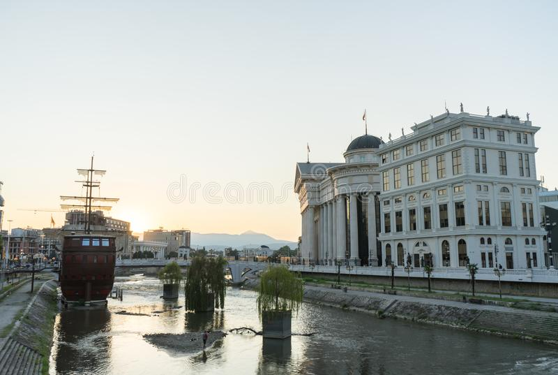 Boot en Restaurant De zonsondergang in centrale Skopje dit onechte galjoenschip zit boven op de Vardar-rivier voor nieuwe Archeol stock fotografie
