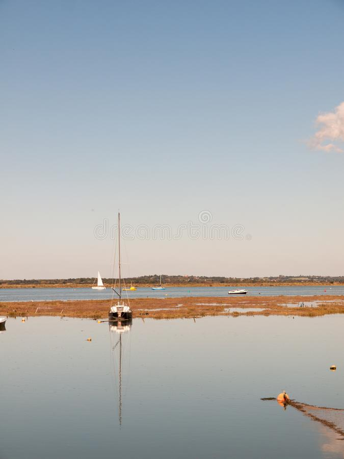 Boot in estuariumscène wordt met mast in water blauw s wordt weerspiegeld vastgelegd dat stock afbeeldingen