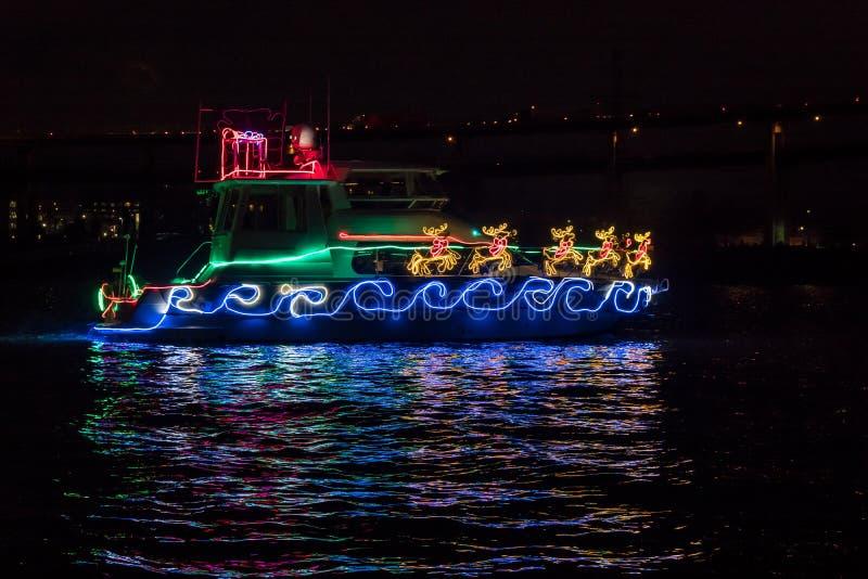 Boot geschmückt mit Weihnachtslichterkette, -Santa Claus Sleigh und -ren und -reflexion im Wasser lizenzfreies stockbild