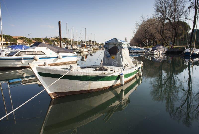 Boot in het Villaggio del Pescatore dok wordt gedokt dat stock afbeelding