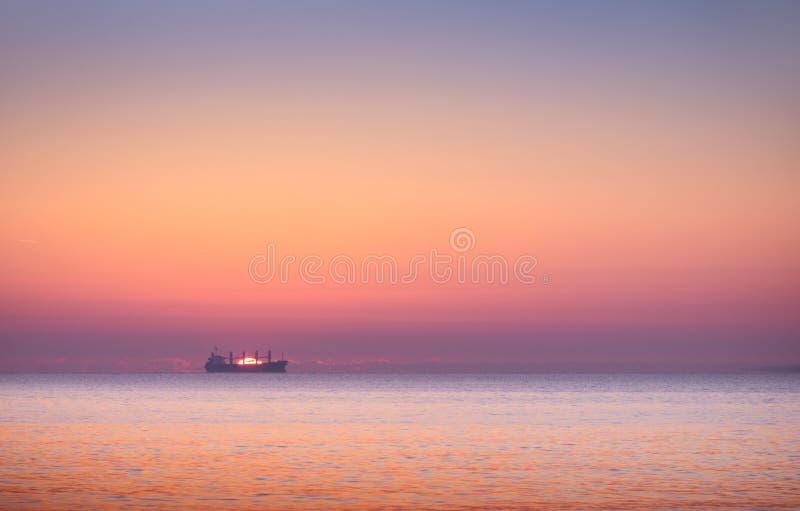 Boot im Meer am Sonnenuntergang lizenzfreies stockbild