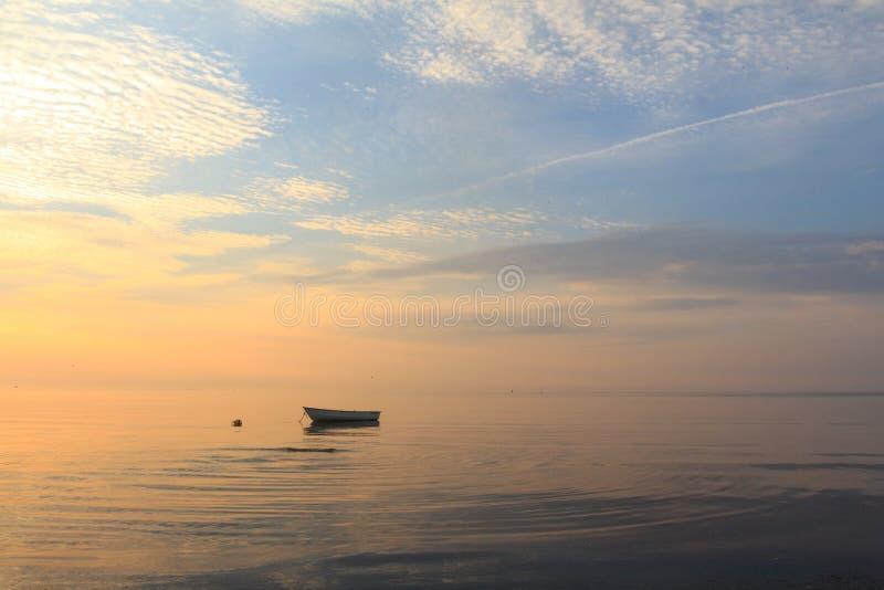 Boot im Ozean bei Sonnenaufgang lizenzfreie stockbilder