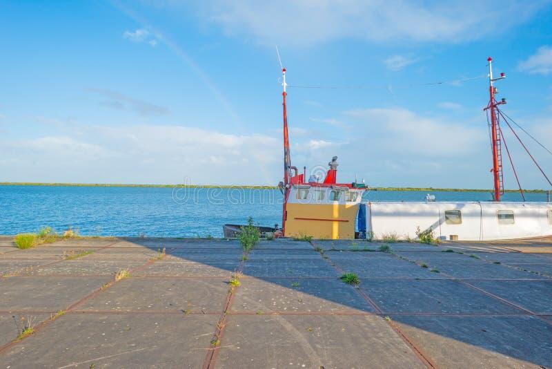 Boot langs een kade in zonlicht wordt vastgelegd dat royalty-vrije stock afbeeldingen