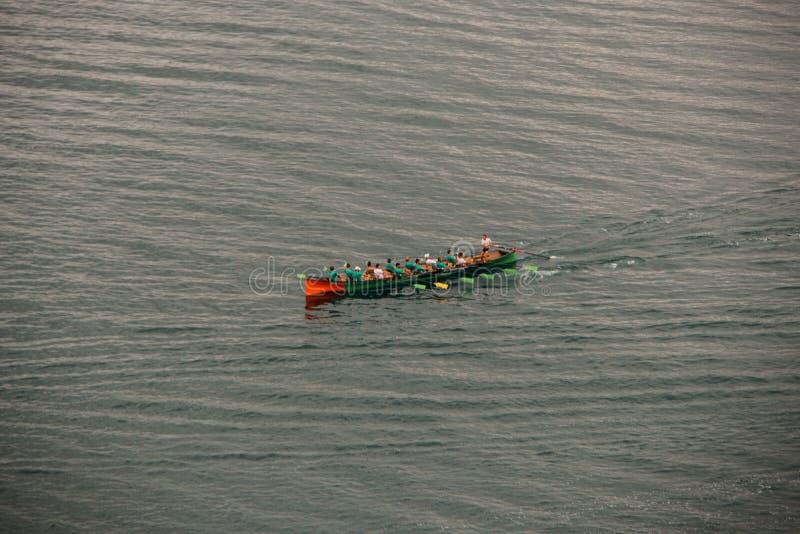 Boot met mensen die in het overzees roeien royalty-vrije stock afbeelding