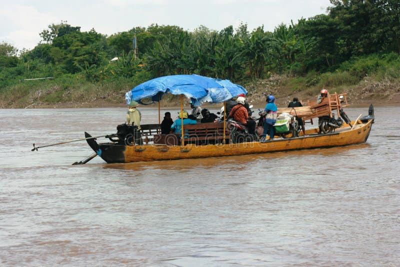 Boot mit den vollen Passagieren, die den Bengawan Solo Fluss kreuzen stockfotografie