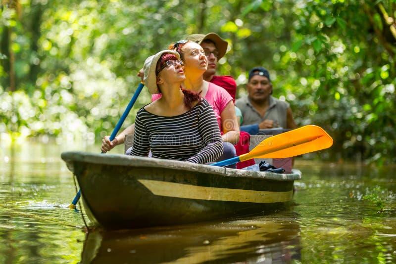 Boot mit Touristen im amazonischen Dschungel lizenzfreie stockbilder