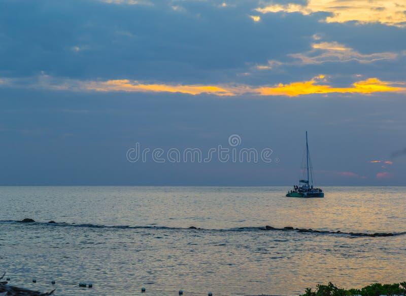 Boot op het Caraïbische overzees bij zonsondergang bij Groot Palladium bij nacht royalty-vrije stock afbeeldingen