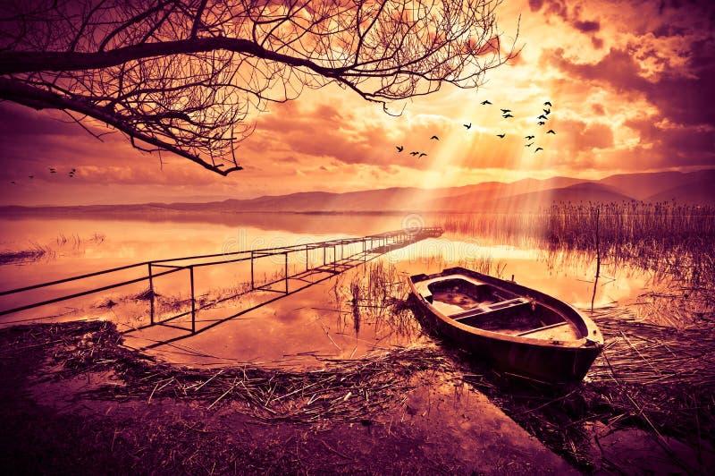Boot op het meer bij zonsondergang royalty-vrije stock afbeeldingen