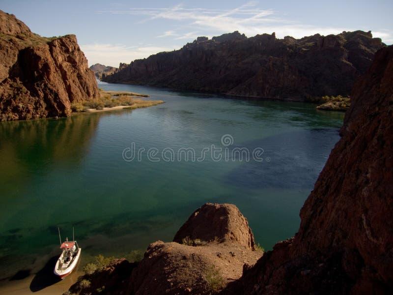 Boot op rivier in woestijnlandschap stock fotografie