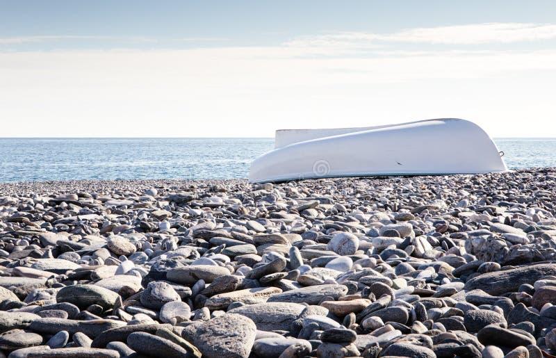 Boot op steenachtig strand stock foto's
