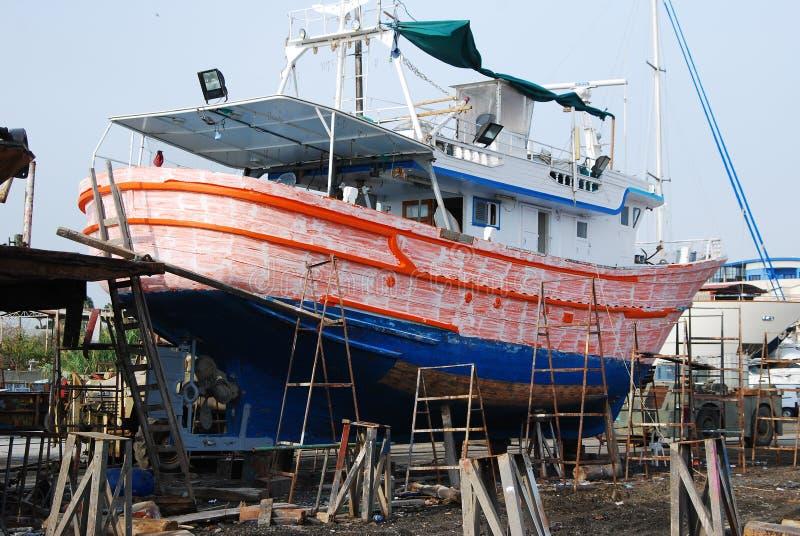 Boot op steiger die gerenoveerd krijgen stock fotografie