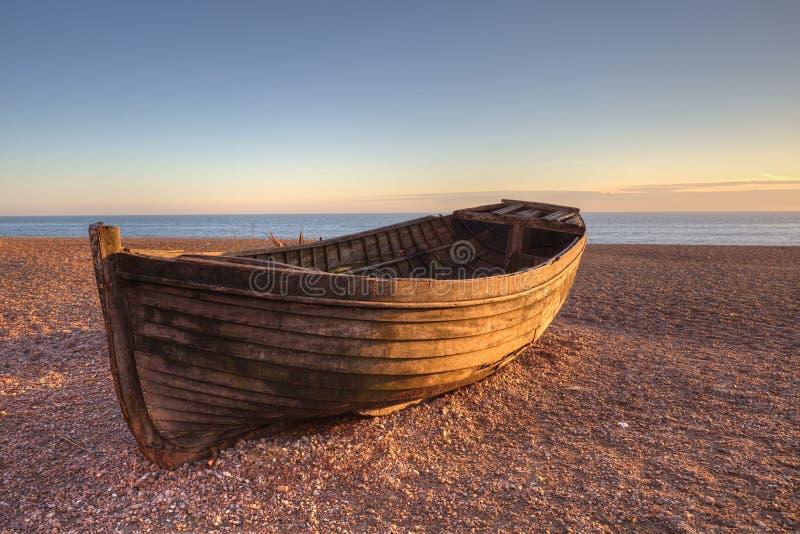Boot op strand door zonsondergang royalty-vrije stock foto
