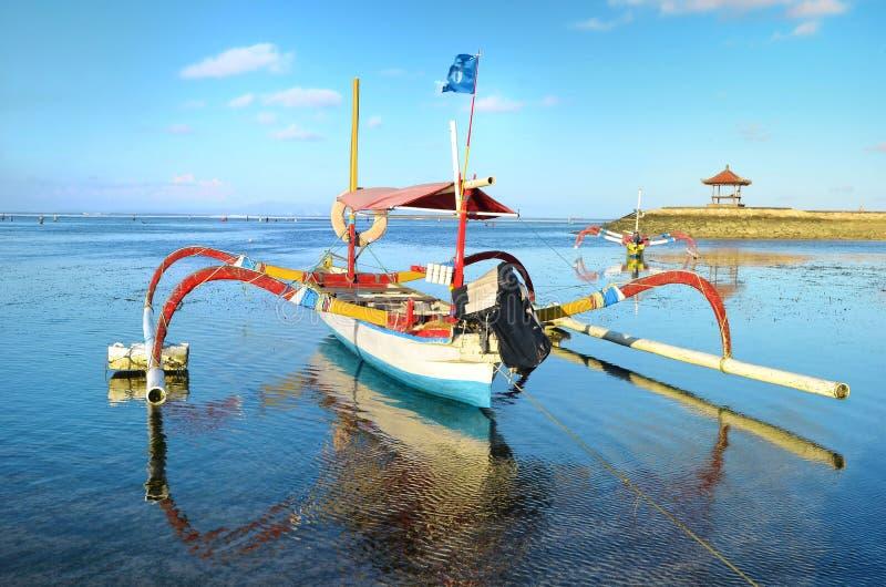 Boot op strand in zonsondergangtijd at low tide stock foto