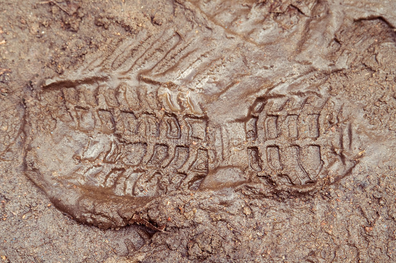 Boot print in brown mud stock images