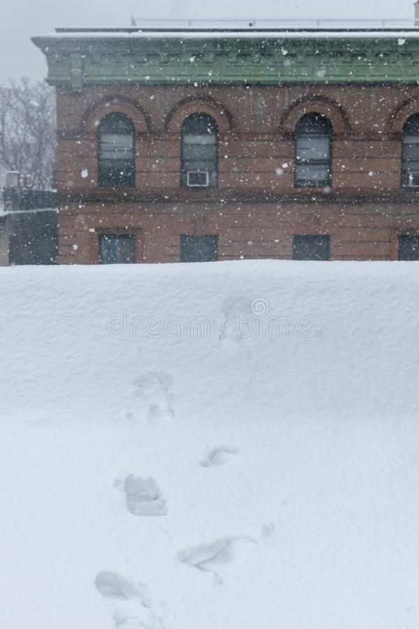 Boot-prints leading toward the edge of a rooftop during heavy snowfall stock photography