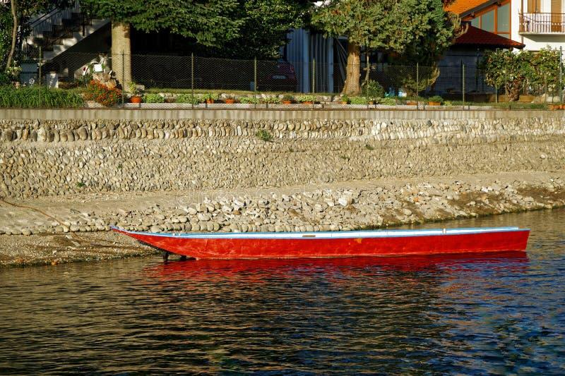 Boot in rode kleur op meer met een bezinning in het water, Exemplaar Ruimtegebied royalty-vrije stock foto's