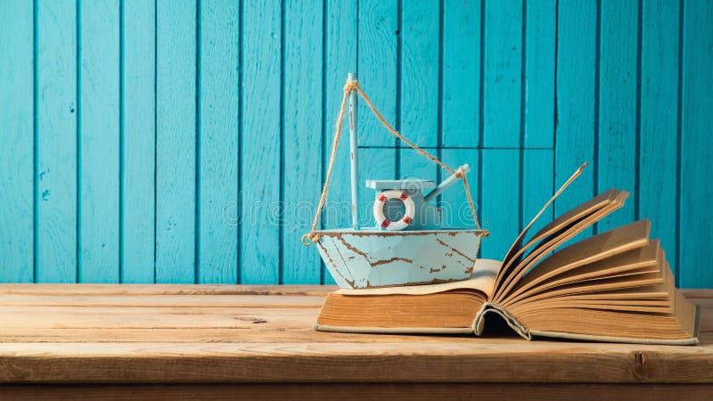 Boot und Buch auf Holztisch stockfotografie