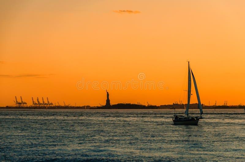 Boot und das Freiheitsstatue Sonnenuntergangschattenbilder lizenzfreies stockfoto