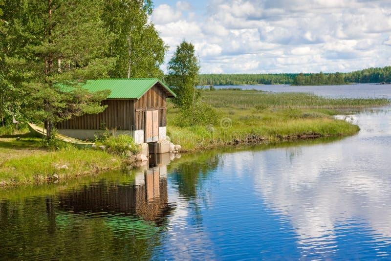 Boot und hölzernes Haus auf dem See in Finnland lizenzfreie stockfotografie