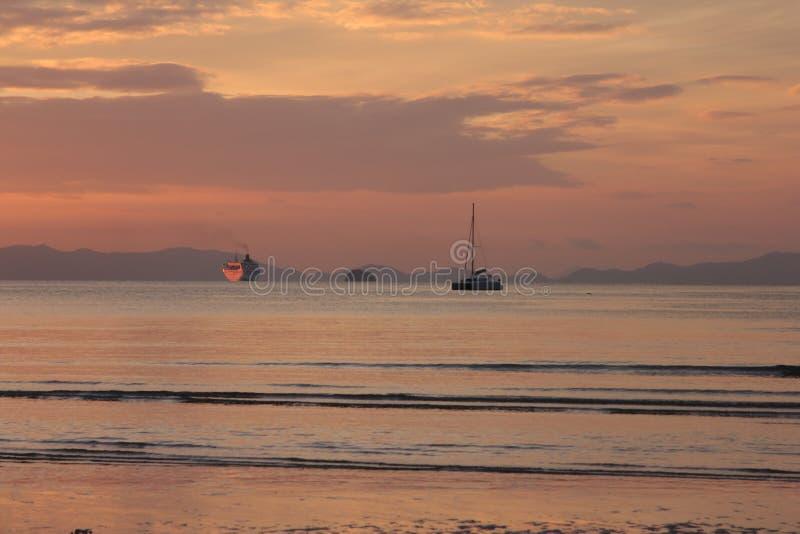 Boote, die weg zum Sonnenuntergang segeln stockfotografie