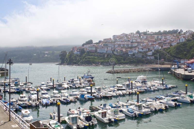 Boote in einem Hafen in Lastres mit dem Dorf hinten, Asturien stockfoto