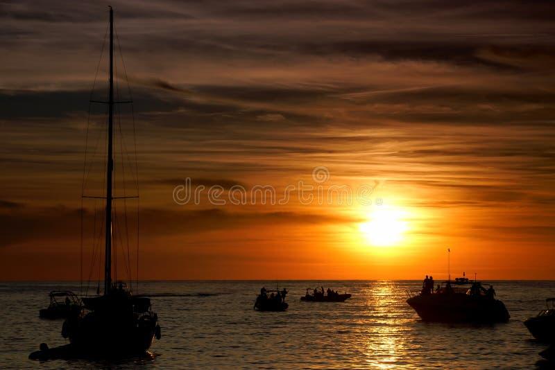 Boote im Sonnenuntergang auf Sonnenuntergang-Streifen bei Sant Antoni de Portmany, Ibiza, Spanien lizenzfreies stockbild